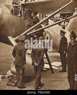 'With the Royal Air Force', 1936 (1937). King Edward VIII on a RAF inspection tour climbs the ladder to look in the cockpit. From Coronation Souvenir  - Stock Photo