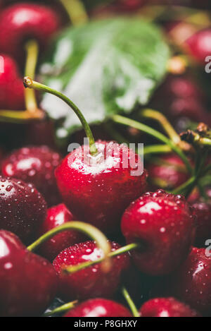 Fresh sweet cherry texture, wallpaper and background. Wet sweet cherries with leaves, selective focus, close-up, vertical composition. Summer food or  - Stock Photo