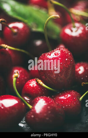 Fresh sweet cherry texture, wallpaper and background. Wet sweet cherries with leaves on dark background, selective focus, close-up, vertical compositi - Stock Photo