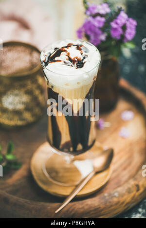 Iced mocha coffee with whipped cream, ice cream and chocolate sauce, served in tall glass over wooden textured background. Summer beverage concept - Stock Photo