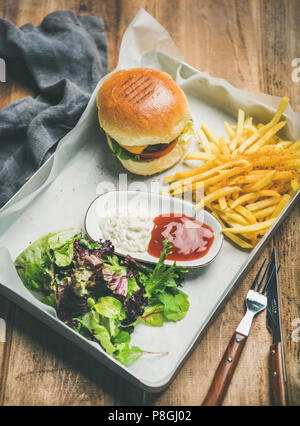 Classic burger dinner. Beef meat homemade burger with French fries, salad and sauces on white tray over rustic wooden table background - Stock Photo