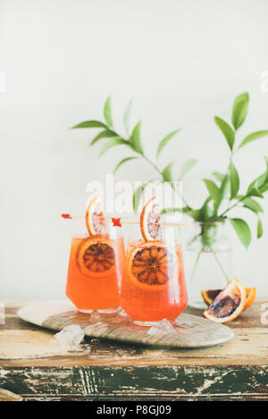 Two glasses of Italian Aperol Spritz alcohol cocktail with ice and blood orange slices on wooden table, copy space. Summer refreshing cocktail drink w - Stock Photo
