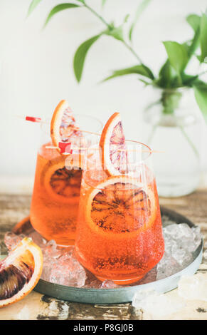 Italian Aperol Spritz alcohol cocktail with ice and blood orange slices on table, vertical composition. Traditional Aperol Spritz cocktail. Summer ref - Stock Photo