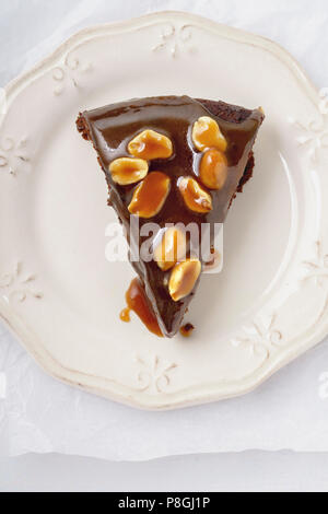 A piece of brownie cake with salted caramel and roasted peanuts - Stock Photo