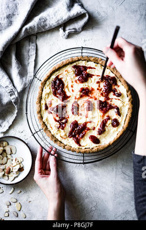 Cooking of an Italian Jam and Ricotta Tart on a gray background - Stock Photo