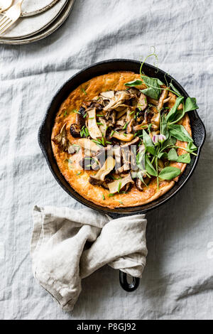 Wild Mushroom Savory Dutch Baby pancake with Pea Greens - Stock Photo
