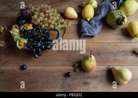 Seasonal autumn fruit on rustic wooden background - Stock Photo