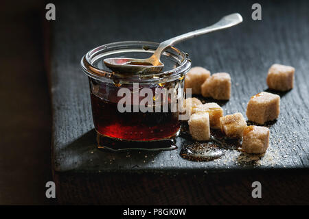 Homemade liquid transparent brown sugar caramel in glass jar standing on black wooden board with spoon and can sugar cubes. Close up. Day light - Stock Photo