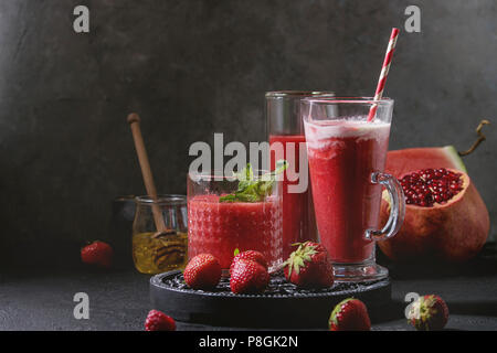 Three different red fruit berry watermelon, strawberry, raspberry, pomegranate cocktails or smoothies in glasses with crushed ice, mint and ingredient - Stock Photo