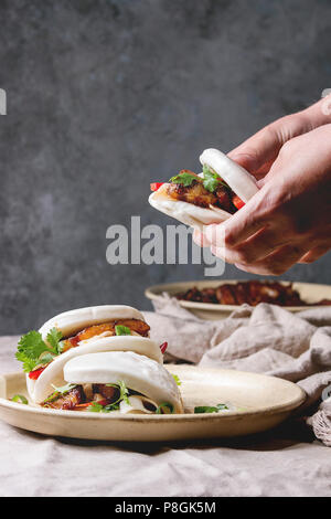 Man's hands hold asian sandwich steamed gua bao buns with pork belly, greens and vegetables served in ceramic plate on table with linen tablecloth. As - Stock Photo