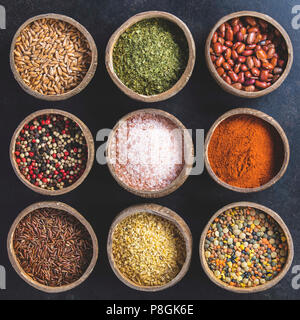 Set of spices on dark rustic background. Coconut shell bowls with paprika salt parsley and pepper. Cooking concept - Stock Photo