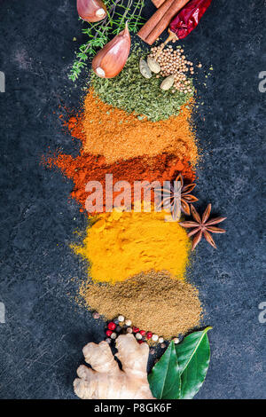Spices and herbs on a dark background. Paprika, parsley, cumin, curcuma, pepper, anice and mustard seeds. Cooking and healthy eating concept - Stock Photo