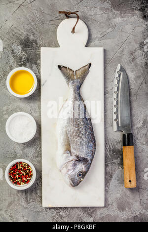 Delicious fresh sea bream fish on marble board, herbs and spices over grey stone background. Cooking concept - Stock Photo