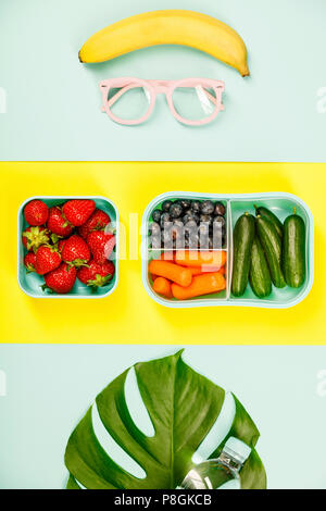 Creative flat lay with glasses, healthy lunch and monstera leaf on pastel colors background - Stock Photo