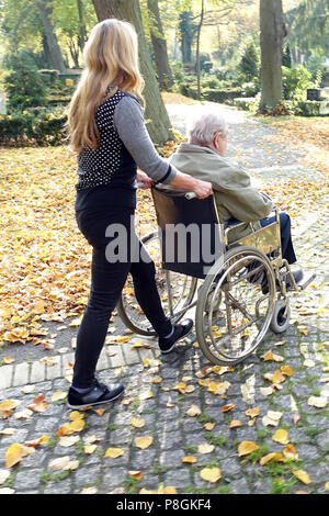 Berlin, Germany, woman pushes an old man in a wheelchair - Stock Photo