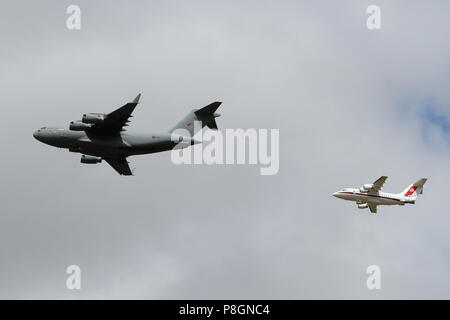 RAF Boeing C-17A Globemaster from 99 Squadron leads a BAe 146 from 32 (The Royal) Squadron over Ipswich during the 100 years RAF Anniversary flypast. - Stock Photo