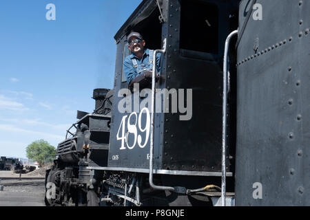 Portrait of a Train engineer on the Cumbres and Toltec scenic Railroad posing with the  restored steam engine 489, a K–39 mikado class locomotive - Stock Photo