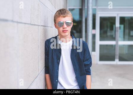 Serious teen wearing sunglasses and leaning against a brick wall. - Stock Photo