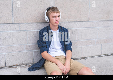 Bored teen sitting on the ground against a wall while listening to music through headphones. - Stock Photo