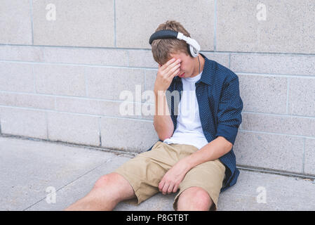 Upset teen sitting on the ground against a wall while listening to music. - Stock Photo