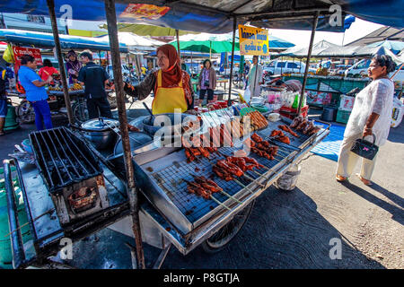 Khao Lak, Thailand - February 22, 2016:  Unknown local merchant with her mobile stall during morning market offering variety of grilled meat on stick. - Stock Photo