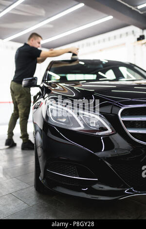 Car detailing - Worker with orbital polisher in auto repair shop. - Stock Photo