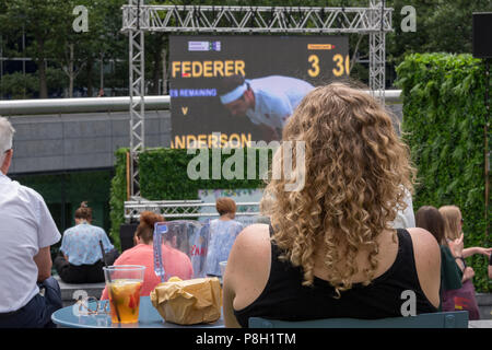 London, UK.11th July, 2018. The Scoop, More London place, Central London. A young woman sitting with a cool drink watches the Wimbledon tennis championships 2018 on a large screen as part of the 'summer by the river' initiative as Roger Federer loses his quarter final match against Kevin Anderson and loses his chance of realising his dream of winning another grand slam championship. Credit: Steve Hawkins Photography/Alamy Live News - Stock Photo