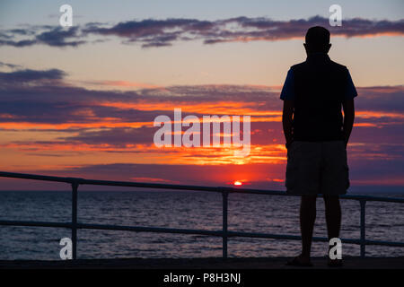 Aberystwyth Wales UK, 11 July 2018. UK Weather:  A man watches as the sun sets on yet another England football World Cup dream, with the team being beaten 2-1 by Croatia after extra time in the semi final. The years of hurt continue for a side who last won the tropy in 1966, and have not been further than the semi final since  then  photo © Keith Morris / Alamy Live News - Stock Photo