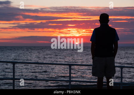 Aberystwyth Wales UK, 11 July 2018. UK Weather:  A man watches as the sun sets on yet another England football World Cup dream, with the team being beaten 2-1 by Croatia after extra time in the semi final. The years of hurt continue for a side who last won the tropy in 1966, and have not been further than the semi final since  then  photo © Keith Morris / Alamy Live News