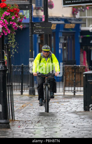 North Wales, 12th July 2018, UK Weather:  An overcast and cooler start to the day for some coupled with the first rain for many weeks with some showers being heavy and thundery, which may cause flooding. A cyclist cycling to work in the rain wearing full rain gear in the market town of Mold, Fliintshire, Wales - Stock Photo
