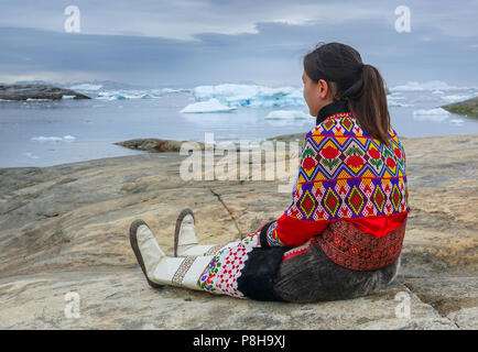 21.06.2018, Gronland, Denmark: A young woman in national costume on July 21st is sitting on a rock in the coastal town of Ilulissat in western Greenland. The city is located on the Ilulissat Icefjord, which is known for its particularly large icebergs in Disko Bay. Photo: Patrick Pleul/dpa-Zentralbild/ZB | usage worldwide - Stock Photo