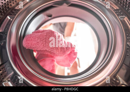 Young man doing laundry view from the inside of washing machine - Stock Photo