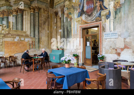 Sedile Dominova, a historic building with an open loggia with original frescos now serving as a working men's club, Two old men playing cards, Sorrent - Stock Photo