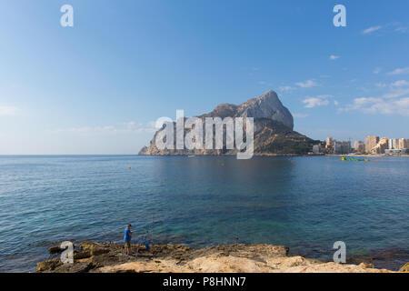 Peñón de Ifach mountain landmark Calp Costa Blanca Spain with fisherman fishing on the rocks - Stock Photo