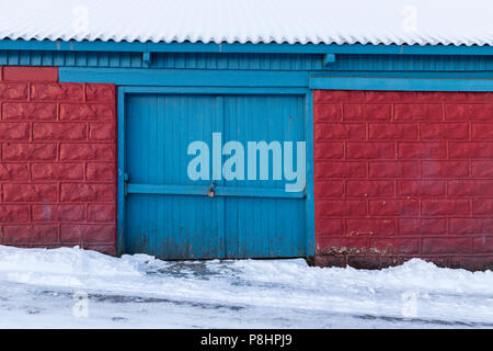 Locked gate of old wooden shed, red bricks with blue door, roof and road covered in winter snow - Stock Photo