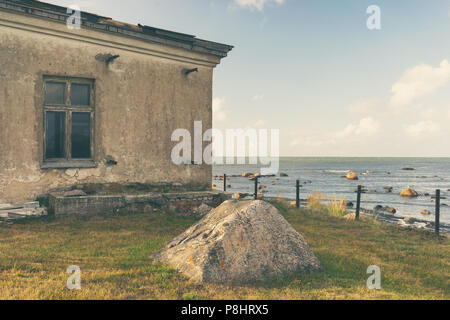 A stone fisherman's house on the shore of the Baltic Sea next to the Tahkuna lighthouse on the background of the horizon - Stock Photo