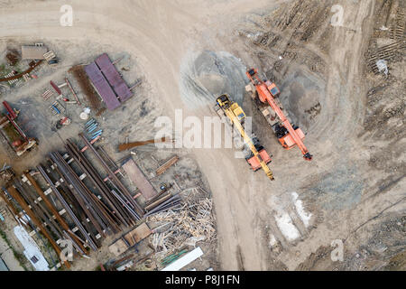 Aerial top view: constraction crane or trucks go together country road  on the construction site to start construction of a new residential complex in - Stock Photo