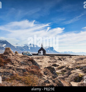16 April 2018: Budir, Snaefellsnes Peninsula, West Iceland - The Black Church and a Volkswagen campervan with bikes on the back, with moss covered... - Stock Photo