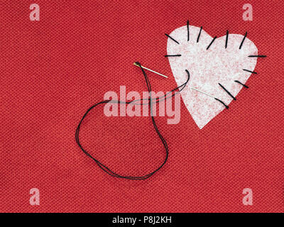 Fabric heart red with white patch and black sewing thread. Mend broken heart concept. - Stock Photo