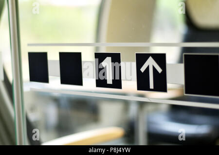 Glass door in a train compartment with a 1 symbolizing first class and arrow - Stock Photo