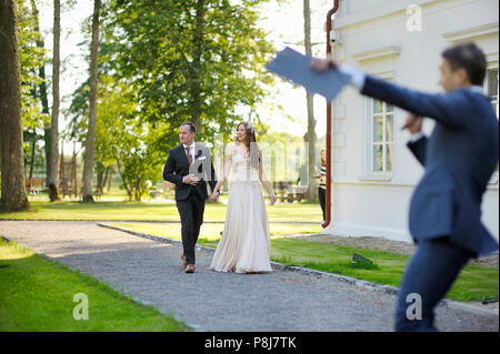 Young bride and groom being greeted by their wedding guests at the wedding reception - Stock Photo