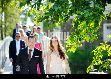 Young bride and groom and their wedding guests in beautiful summer park - Stock Photo