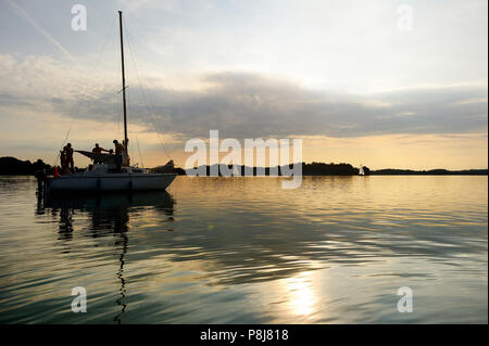 Yacht sailing towards sunset on Trakai lake in Lithuania - Stock Photo