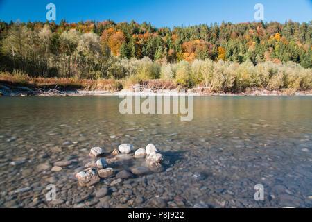 The river Lech with autumnal forest near the Ziegelwiesen, Füssen, Bavaria, Germany