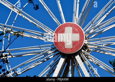 Closeup of a ferris wheel in Geneva, Switzerland, with the round center piece made of red and white lights configured into a Swiss flag. - Stock Photo