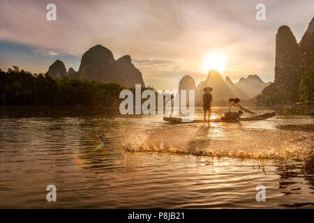Cormorant Fisherman casting net on Li river, Xingping, Guilin China, as the sun sets behind the karst mountains behind him. - Stock Photo