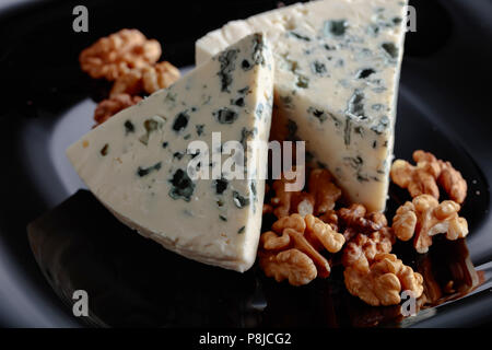 Wedges of soft blue cheese with walnuts on a black plate. - Stock Photo