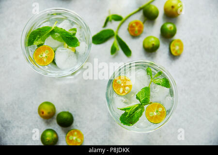 Two glass of gin and tonik cocktail with green calamondin and fresh mint leaf. - Stock Photo