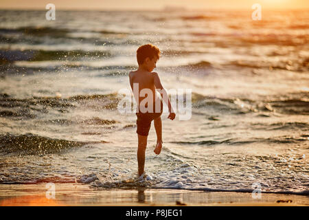 Silhouette of happy little boy jumping in sea at sunset - Stock Photo