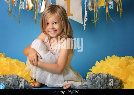Portrait of happy surprised little girl in princess dress with open mouth and waving hands isolated on blue background - Stock Photo